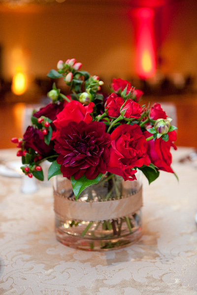 Low centerpieces of burgundy dahlias red roses and red hypericum berries